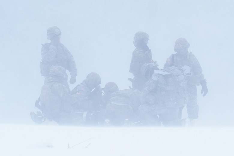 Medics from the 6th Brigade Engineer Battalion (Airborne), 4th Infantry Brigade Combat Team (Airborne), 25th Infantry Division, U.S. Army Alaska, prepare a simulated casualty for transport at an extraction point while training with aviators from the Alaska Army National Guard at Neibhur Drop Zone, Nov. 26, 2019, to hone their life-saving and Medevac hoist skills for the paratroopers' upcoming rotation to the Joint Readiness Training Center at Fort Polk, La.