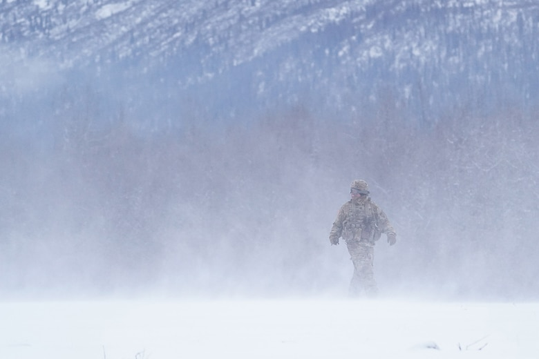 A soldier assigned the 6th Brigade Engineer Battalion (Airborne), 4th Infantry Brigade Combat Team (Airborne), 25th Infantry Division, U.S. Army Alaska, smiles as he looks into a helicopter's rotor wash while training with aviators from the Alaska Army National Guard at Neibhur Drop Zone, Nov. 26, 2019, to hone their life-saving and Medevac hoist skills for the paratroopers' upcoming rotation to the Joint Readiness Training Center at Fort Polk, La.