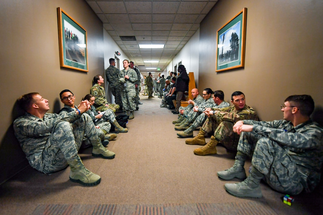Members of the 50th Space Wing execute tornado warning emergency procedures during exercise Opinicus Vista 19-3 in Building 300 at Schriever Air Force Base, Colorado, Nov. 19, 2019.