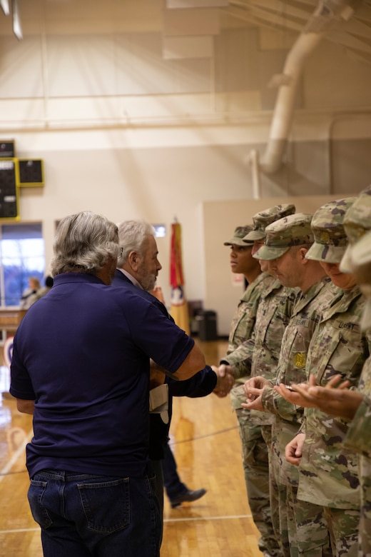 American Legion Hardin Post 113 personnel hand out coins to deploying 1st Theater Sustainment Command (TSC) Soldiers during a deployment ceremony on Nov. 26, 2019 at Sadowski Center, Fort Knox, Ky.