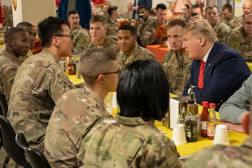 President Donald J. Trump speaks with service members  while they eat.