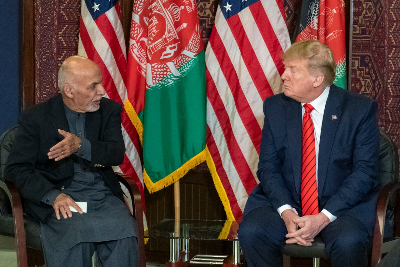 Two leaders sit in chairs and talk with flags behind them.