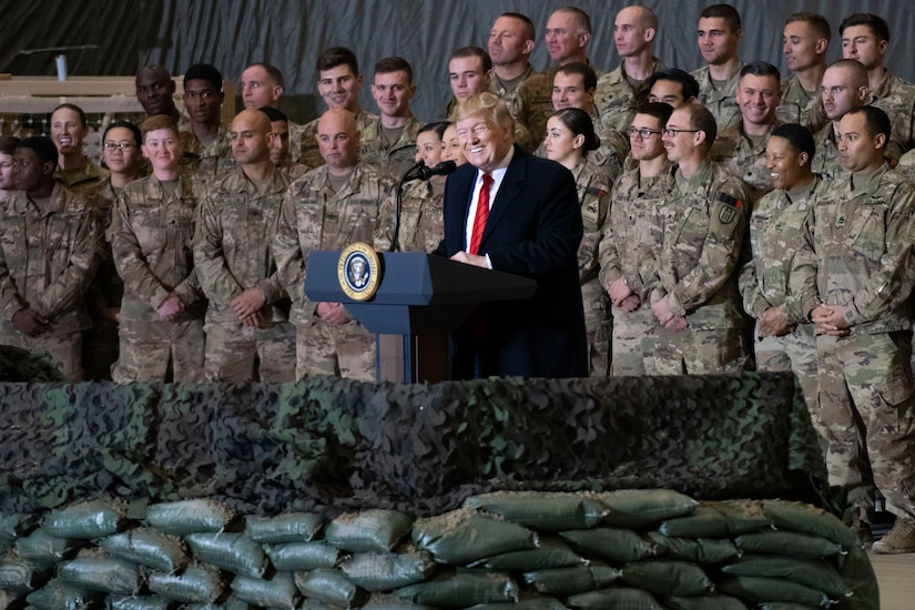 A man speaks from behind a podium surrounded by military members.