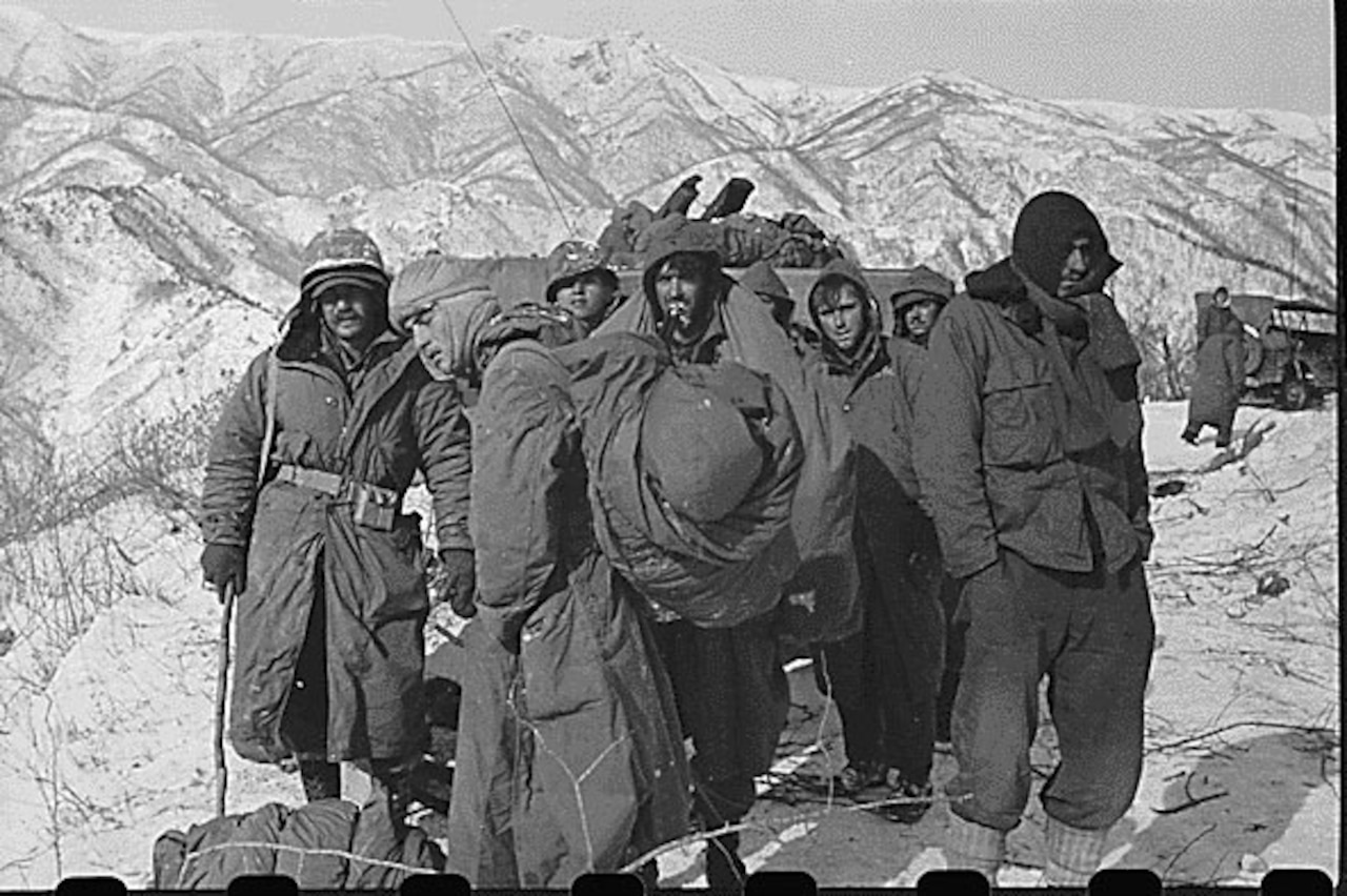 Several men in parkas and heavy clothing stand around together, with snow-covered mountains in the background.