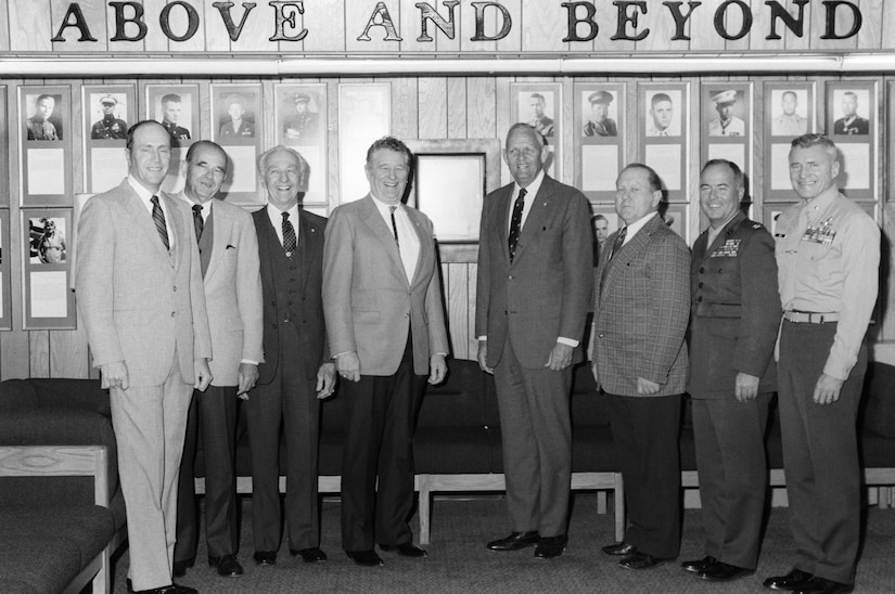 "Eight Medal of Honor recipients pose in front of a wall of plaques and photos with the words ""Above and Beyond."""