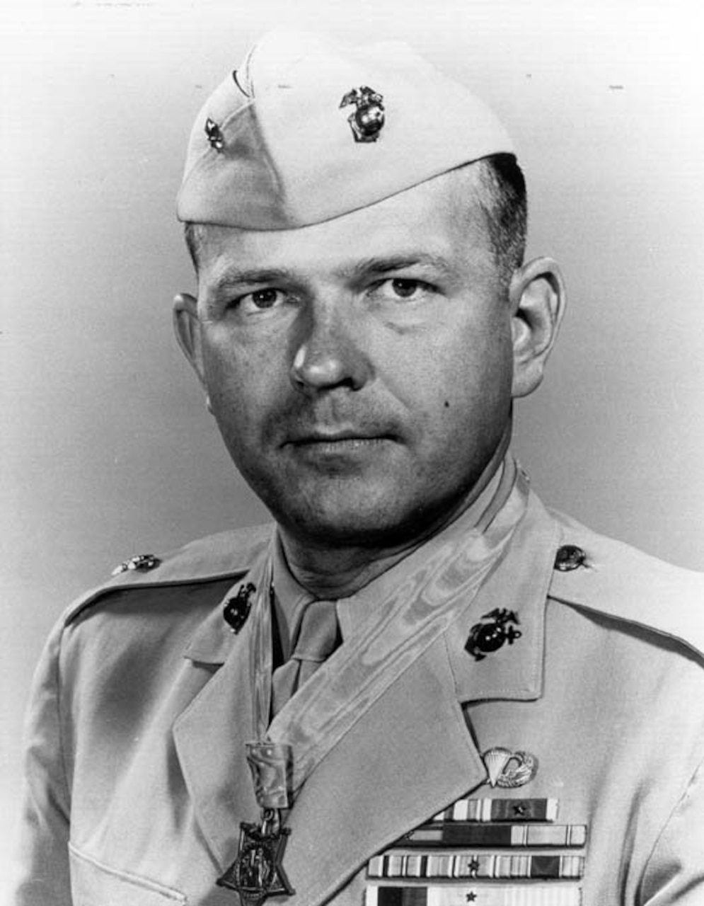 Photo of a Marine Corps colonel wearing his khaki dress uniform, cap and Medal of Honor.