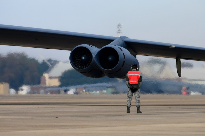 An airmen stands in front of a B-52 Stratofortress jet engine.