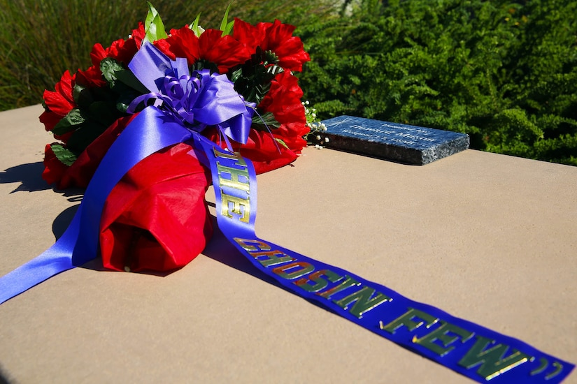 "A wreath with a blue ribbon that reads ""The Chosin Few"" sits on top of a large grave marker."