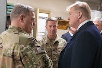 Three leaders stand together and talk.