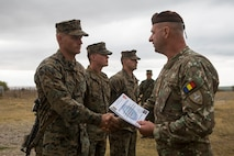 U.S. Marines with Marine Rotational Force-Europe 19.2, Marine Forces Europe and Africa, receive certificates from a Romanian soldier with the 341st Infantry Battalion during the exercise Platinum Eagle closing ceremony in Babadag Training Area, Romania, Sept. 19, 2019.