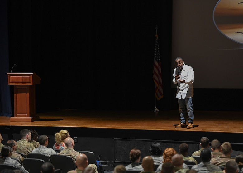 A man stands on a stage and speaks to Airmen.