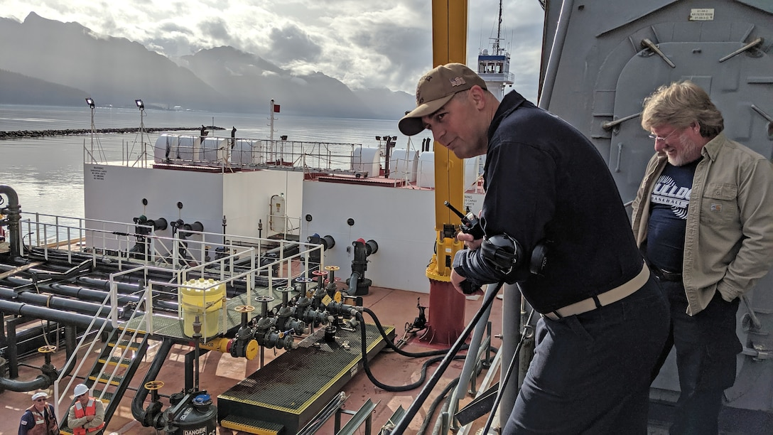 men observe refueling operations on a ship