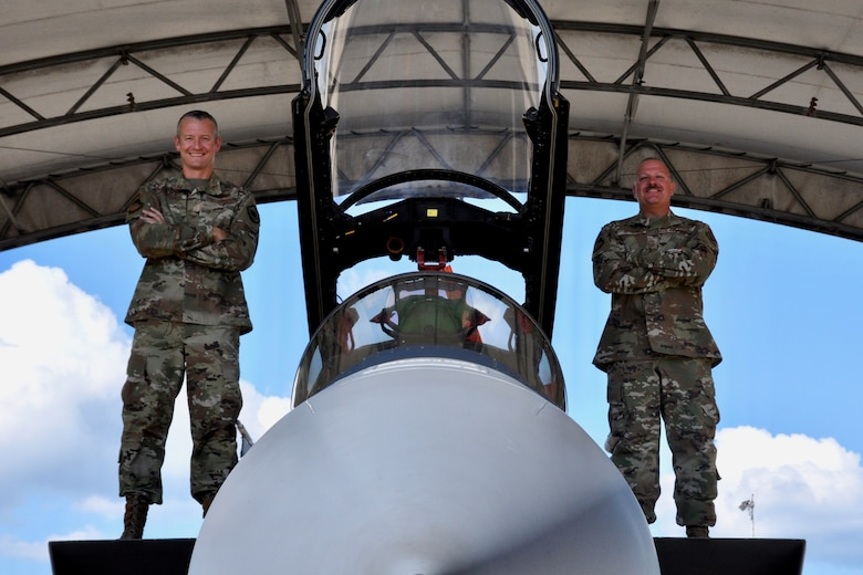 U.S. Air Force Col Ryan Messer, 53rd Wing Commander, and U.S. Air Force Chief Master Sgt. Justin Apticar, 53rd Wing Command Chief, pose on an F-15E Strike Eagle for a command team photo.