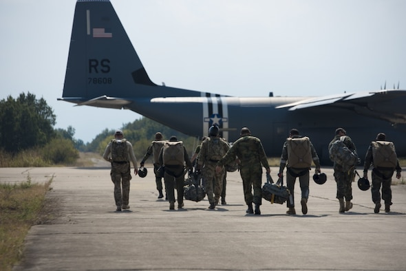 A group of jumpers with Bulgaria's 68th Special Forces Brigade and U.S. military jumpmasters walk out to a 37th Airlift Squadron C-130J Super Hercules at Cheshnegirovo drop zone in Plovdiv, Bulgaria, Sept. 26, 2019. During Thracian Fall 19, 37th AS airmen and aircraft are providing primary airlift support for Bulgarian 68th SFB members completing a U.S.-sponsored military free fall course. (U.S. Air Force photo by Staff Sgt. Kirsten Brandes)