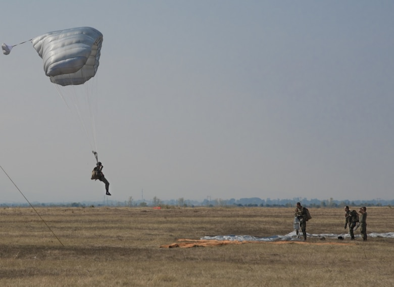 A jumper with Bulgaria's 68th Special Forces Brigade glides into Cheshnegirovo drop zone in Plovdiv, Bulgaria, Sept. 26, 2019. The students of the military free-fall course, using steerable parachutes, were expected to aim for the large orange tee. (U.S. Air Force photo by Staff Sgt. Kirsten Brandes)