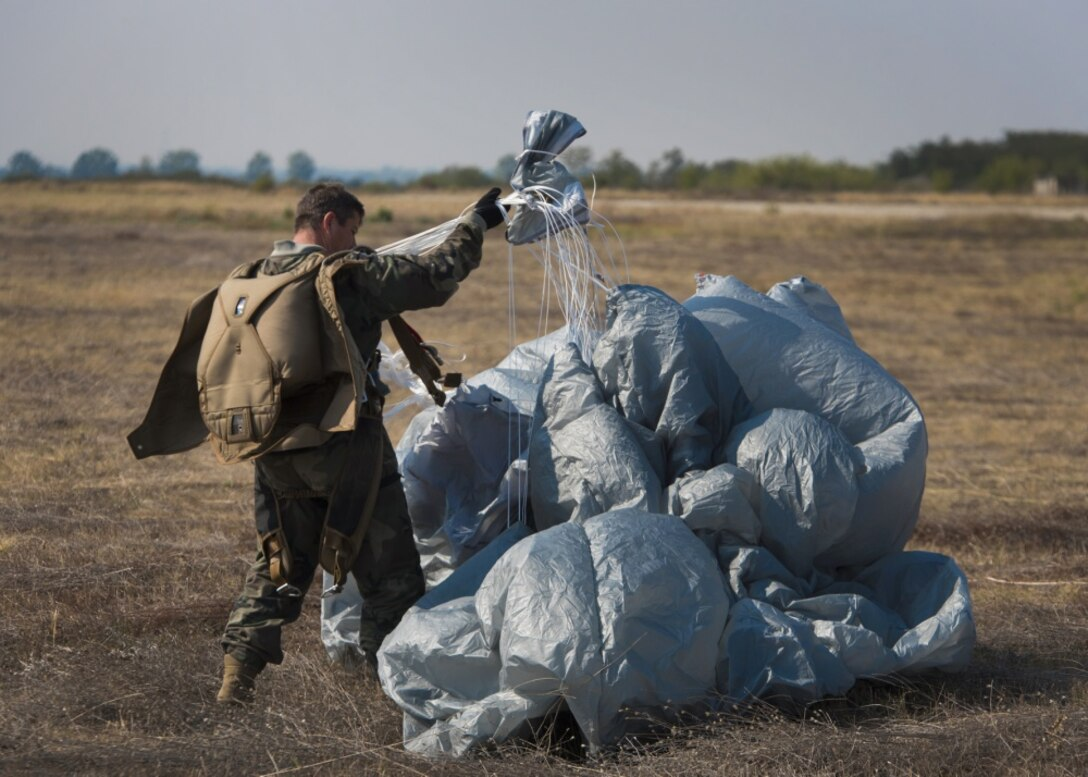 A jumper with Bulgaria's 68th Special Forces Brigade recovers his parachute after a jump into Cheshnegirovo drop zone in Plovdiv, Bulgaria, Sept. 26, 2019. Once the students of the military free-fall course landed, they were expected to recover their parachutes and prepare to jump again. (U.S. Air Force photo by Staff Sgt. Kirsten Brandes)