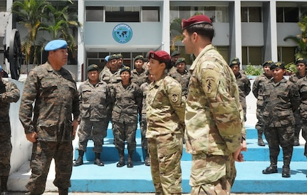 Guatemalan military personnel stand in formation and talk.
