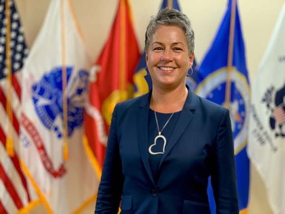 Photo of female in blue business suit standing in front of flags