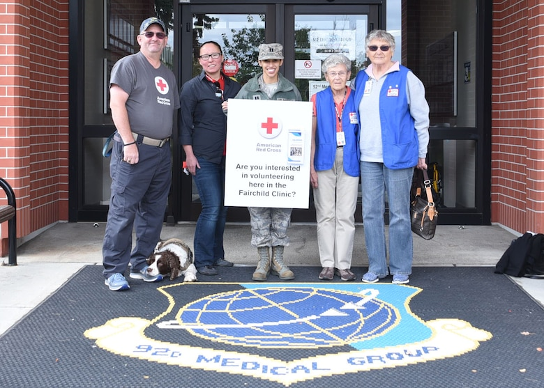 Members from the American Red Cross volunteer program and Capt. Aurora Seefong, 92nd Medical Group Education and Training flight officer, pose in front of Team Fairchild's 92nd MDG.