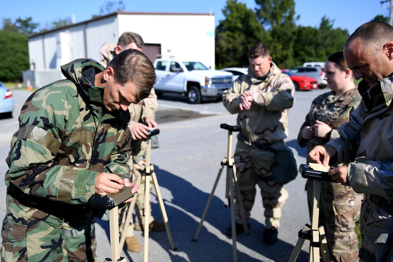 People in CBRN gear look at paper.