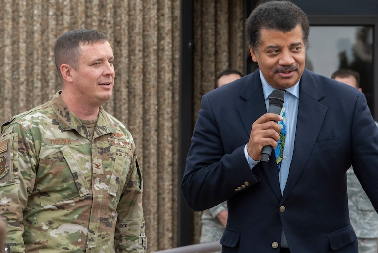 Col. Jack Fischer, 50th Space Wing vice commander, left, stands alongside Neil deGrasse Tyson, astrophysicist and author, while he addresses Airmen at Schriever Air Force Base, Colorado, Sept. 23, 2019. Tyson visited Schriever AFB to understand its mission and to visit with Airmen. (U.S. Air Force photo by Airman 1st Class Jonathan Whitely
