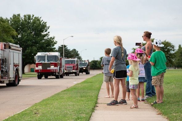 Military children watch the a fire deparptment parade through base housing.