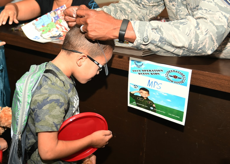 Nathan Guzman, son of Staff Sgt. Benjamin Guzman, 317th Aircraft Maintenance Squadron aircraft debriefer, receives dog tags during Operation Dyess Kids at Dyess Air Force Base, Texas, Sept. 28, 2019.
