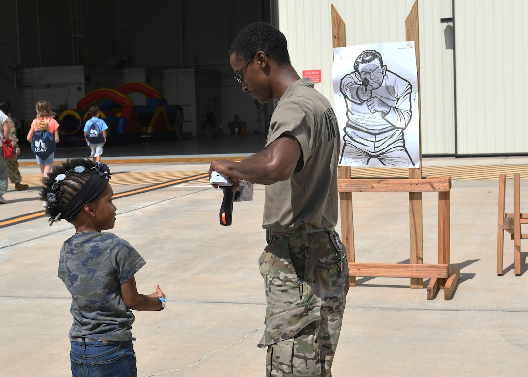 Staff Sgt. Jalen Snyder, 7th Security Forces Squadron combat arms instructor, reloads a toy gun for Sapphire Johnson, daughter of Tech. Sgt. Rebecca Johnson, 489th Bomb Group command support staff NCO in charge, during Operation Dyess Kids at Dyess Air Force Base, Texas, Sept. 28, 2019.