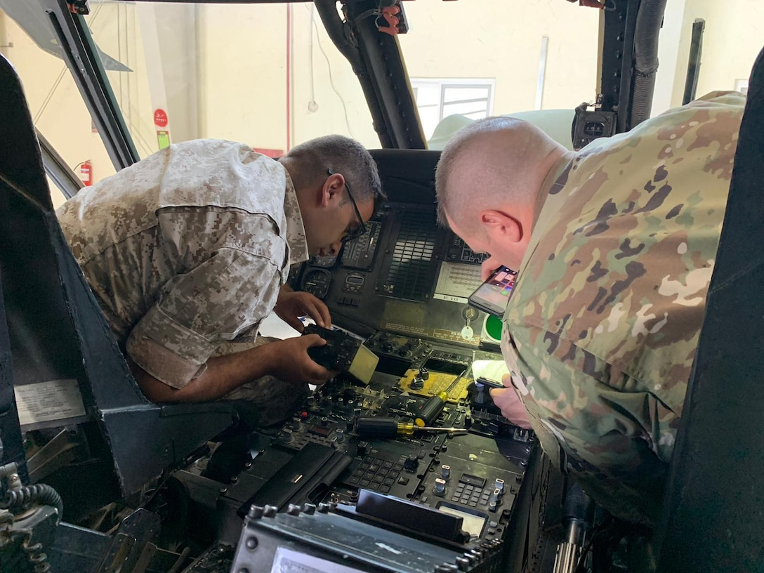 Indiana National Guard Sgt. 1st Class Brain W. Branson talks with a Jordan armed forces service member about helicopter avionics.