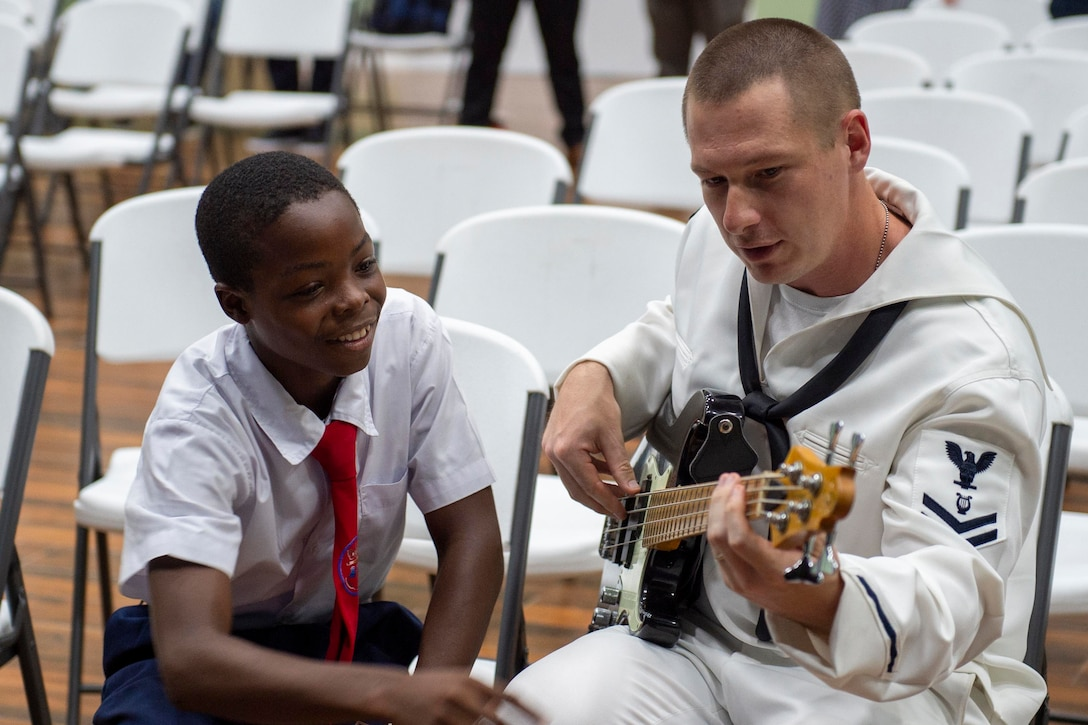 A sailor plays a bass guitar while a young boy smiles and watches.