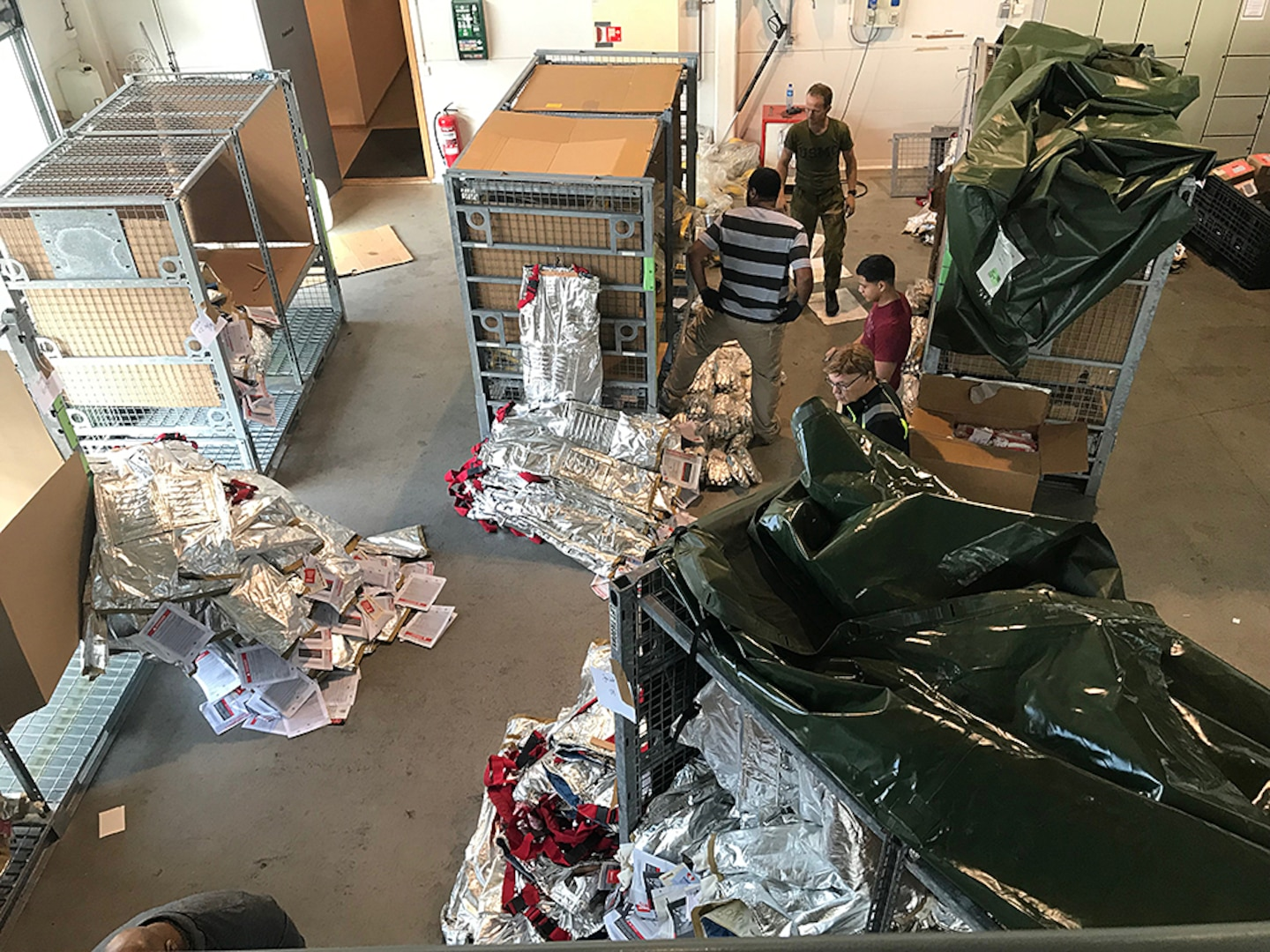 Disposal Services Representative Courtney Aubrey and Property Disposal Specialist Zeke Graham work alongside Norwegian personnel to prepare firefighting suits and other excess material for turn in to DLA at a secure storage facility in Norway.