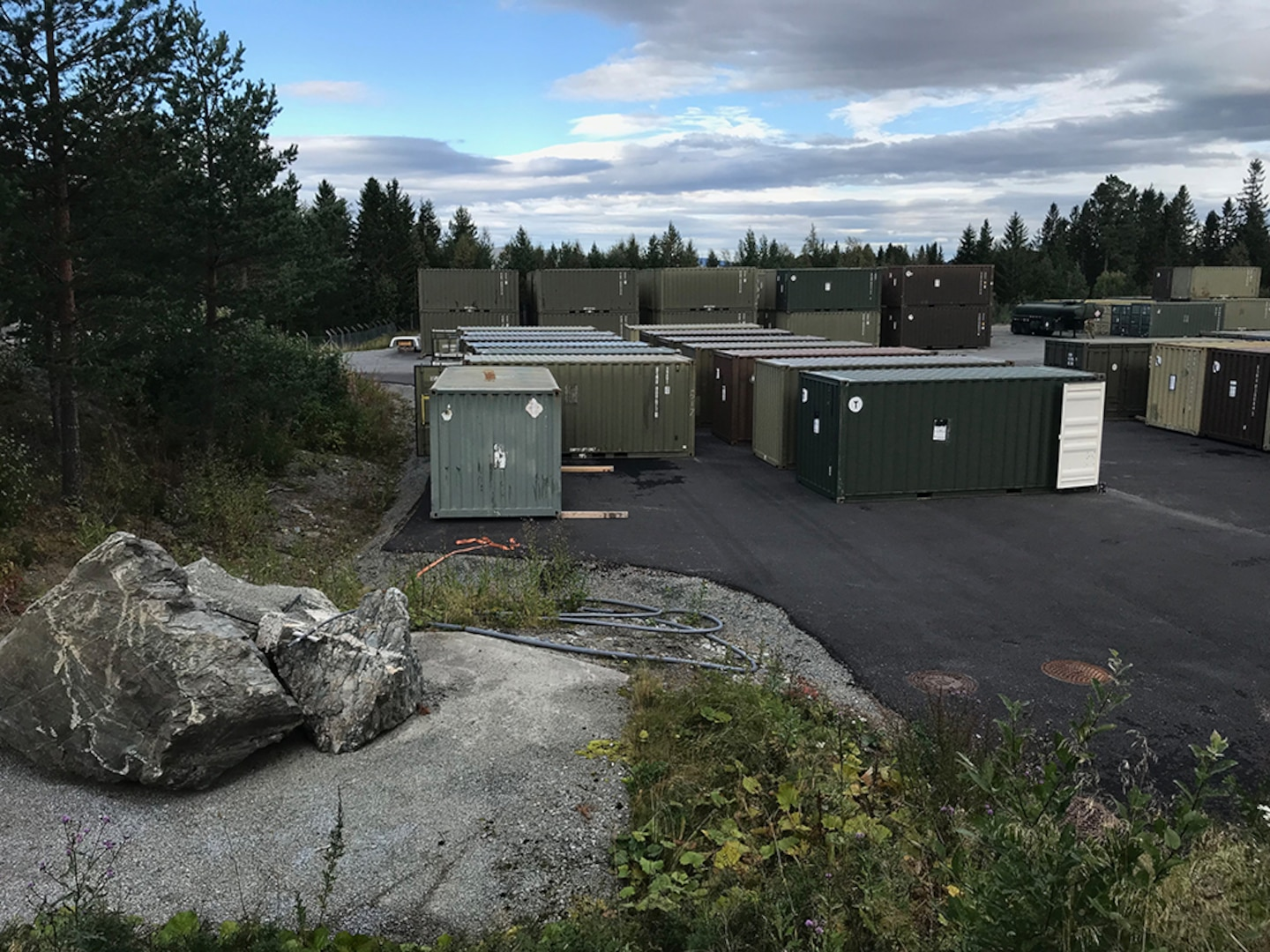 Shipping containers of used, excess and mission-obsolete materials are staged outside a cave facility in Norway, where DLA Disposition Services reps recently visited to help with training and preparation for Marine Corps property disposal.