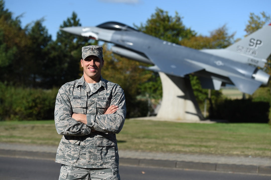 2nd Lt. Nick Weiland poses in front of an F-16 static display at his former unit September 19, 2019, at Spangdahlem Air Base, Germany. Weiland spent two years stationed in Germany as an enlisted Airman and returned in 2019 as an officer with the 132d Logistics Readiness Squadron. (U.S. Air National Guard photo by Staff Sgt. Michael J. Kelly)