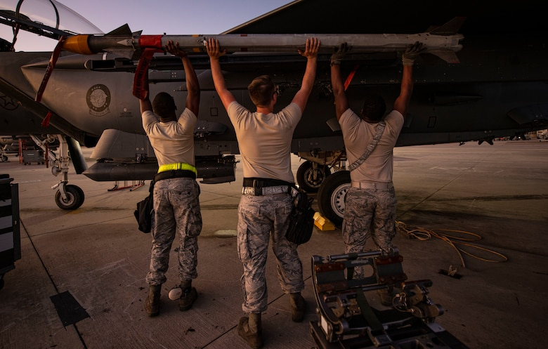 Three aircraft armament systems technicians assigned to the 757th Aircraft Maintenance Squadron load an AIM-9X Sidewinder missile onto an F-15E Strike Eagle fighter jet during Combat Archer 19-12 on Tyndall Air Force Base, Fla., Sept. 24, 2019. The AIM-9X system includes infrared-tracking, air-to-air and air-to-surface capabilities. (U.S. Air Force photo by Airman 1st Class Bailee A. Darbasie)