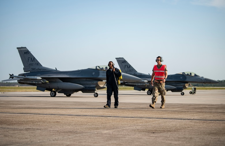 Two tactical aircraft maintainers assigned to the 157th Fighter Squadron walk along the flightline during Combat Archer 19-12 on Tyndall Air Force Base, Fla., Sept. 24, 2019. The F-16 Fight Falcon fighter jets from the 157th FS's integration acted as alert aircraft and simulated an alert scramble replicating a homeland defense mission.  (U.S. Air Force photo by Airman 1st Class Bailee A. Darbasie)