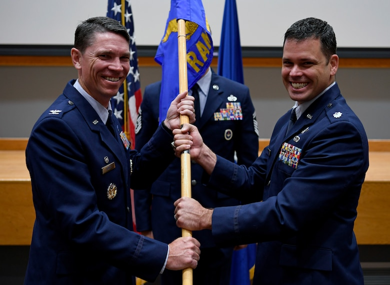 Lt. Col. Peter Francik (right) accepts the guidon and command of the 318th Range Squadron from Col. James Hewitt, 318th Cyberspace Operations Group commander, during the squadron's activation ceremony at Joint Base San Antonio-Lackland, Texas, Oct. 1, 2019. The then-614th Radar Squadron was previously inactivated Aug. 1, 1963, at Cherry Point Marine Corps Air Station, N.C. (U.S. Air Force photo by Tech. Sgt. R.J. Biermann)