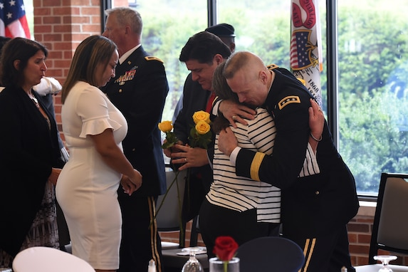Lt. Gen. Thomas S. James Jr., Commanding General, First U.S. Army, hugs a Gold Star Mother after she received a yellow rose during the Gold Star Mother's Day luncheon, September 29, 2019, at Cantigny Park in Wheaton, Illinois.