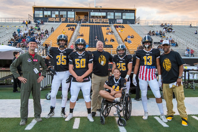 Lt. Col. Ryan Typolt (left), 29th Attack Squadron commander, poses with Alamogordo High School Football players and staff prior to an AHS Military Appreciation Night football game, Sept. 27th, 2019, in Alamogordo, N.M. Typolt was invited to swear-in nine individuals into the Delayed Entry Program. (U.S. Air Force photo by Staff Sgt. Christine Groening)