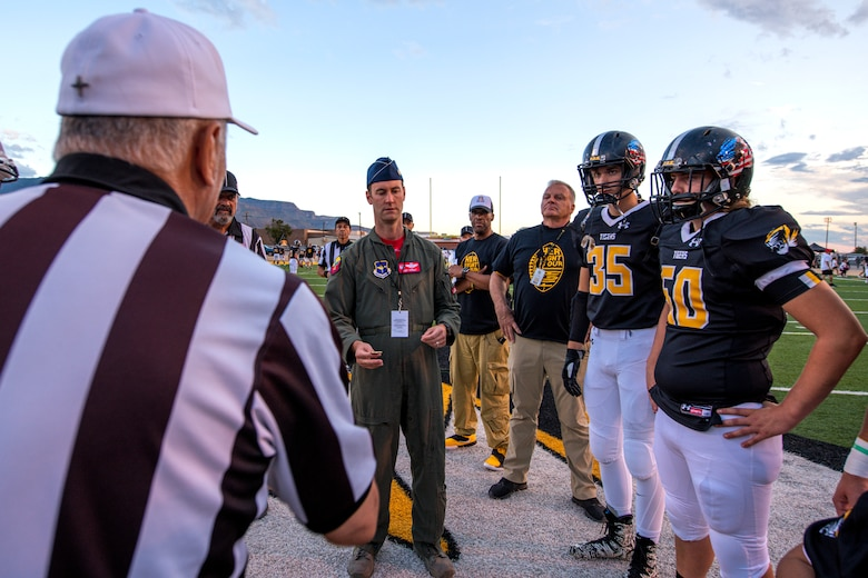 Lt. Col. Ryan Typolt, 29th Attack Squadron commander, prepares to toss a coin prior to an Alamogordo High School Military Appreciation Night football game, Sept. 27th, 2019, in Alamogordo, N.M. Typolt was invited to swear-in nine individuals into the Delayed Entry Program. (U.S. Air Force photo by Staff Sgt. Christine Groening)