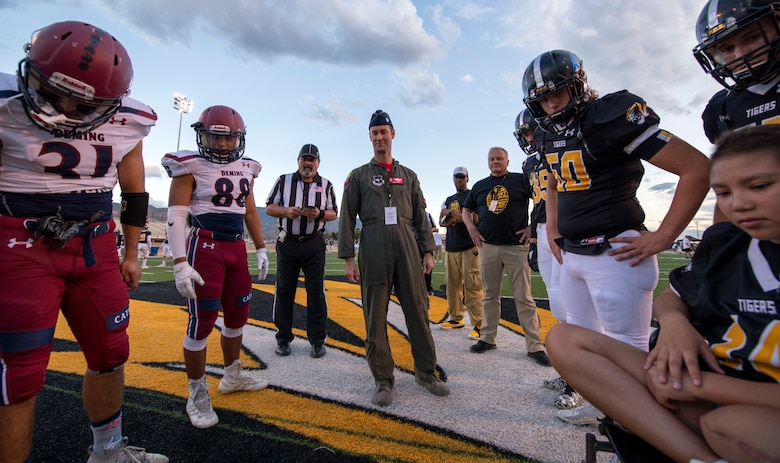 Alamogordo and Demming High School football players and Lt. Col. Ryan Typolt, 29th Attack Squadron commander, look at the pre-game coin toss results during AHS Military Appreciation Night football game, Sept. 27th, 2019, in Alamogordo, N.M. Typolt was invited to swear-in nine individuals into the Delayed Entry Program. (U.S. Air Force photo by Staff Sgt. Christine Groening)