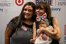"""Leticia, a military spouse, left, poses with her child and Heidi Murkoff, author of the """"What to Expect"""" franchise, during the """"Special Delivery Baby Shower"""", Klipper Ballroom, Marine Corps Base Hawaii, Sept. 19, 2019. The baby shower was open to new and expecting parents and included a question and answer with Murkoff, raffle prizes, games, food, and gifts. This event was sponsored by the United Service Organization and the """"What to Expect"""" franchise. (U.S. Marine Corps photo by Pfc. Samantha Sanchez)"""