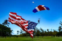 Frank Hinshaw, a volunteer with the Flying Leathernecks, guides the National Colors by parachute to the Kaneohe Klipper Golf Course, Marine Corps Base Hawaii , Sep. 27, 2019.The jump was conducted in support of the third annual Esprit De Corps Golf Tournament's opening ceremony, which is sponsored by the Marine Corps League Hawaii Aloha Detachment 363. The Marine Corps League was founded by Lt. Gen. John A. Lejeune in 1923 allowing  honorably discharged, active duty, and reserve Marines to continue to join in camaraderie and fellowship. (U.S. Marine Corps photo by Sgt. Alex Kouns)