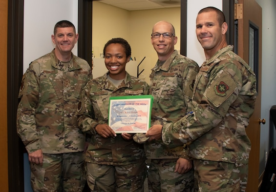 U.S. Air Force Col. Zachery Jiron, right, 60th Air Mobility Wing vice commander, Chief Master Sgt. Derek Crowder, left, 60th AMW command chief, and Capt. Kevin Hostettler, center right, 60th AMW Chapel chaplain recognize Airman 1st Class Kasen Hodges 60th AMW religious affairs journeyman, as the Warrior of the Week, Oct. 1, 2019 at Travis Air Force Base, California. The Warrior of the Week program recognizes an outstanding Travis Airman or noncommissioned officer. (U.S. Air Force photo by Heide Couch)