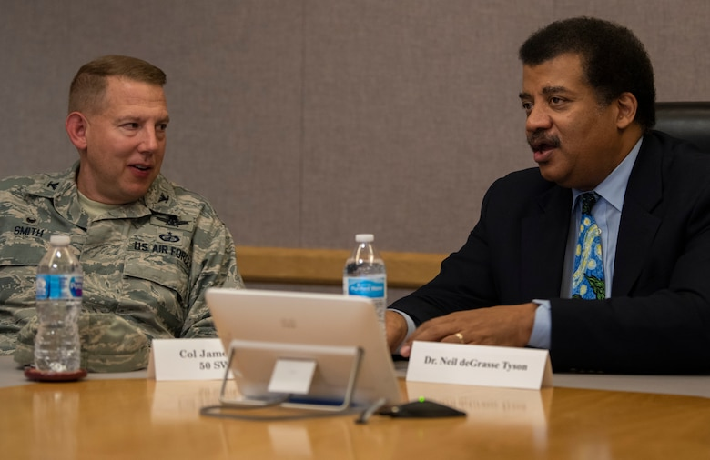 Col. James Smith, 50th Space Wing commander, left, talks to Neil DeGrasse Tyson, astrophysicist and author, during a wing mission brief at Schriever Air Force Base, Colorado, Sept 23. 2019. During the mission brief, Tyson learned about the mission, units and mission partners at Schriever AFB. (U.S. Air Force photo by Airman 1st Class Jonathan Whitely)