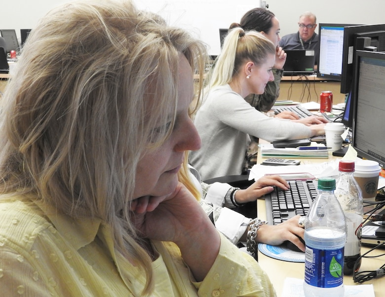 Lisa Cupp, AFIMSC Detachment 10 resources division chief, updates spreadsheets after phone discussion with the Malmstrom AFB, Mont., comptroller. (Air Force photo by Ed Shannon)