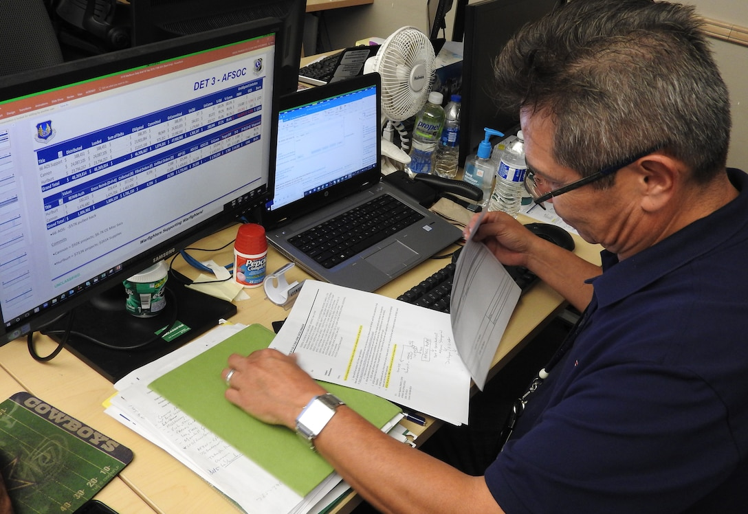 Frank Sinche, an AFIMSC base analyst for Air Force District of Washington and Air Force Special Operations Command units, reviews funding requirements in preparation for briefing members of the war room on closeout status. (Air Force Photo by Ed Shannon)