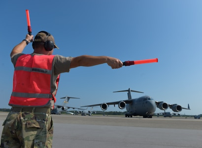 U.S. Air Force Master Sgt. Jeffery Smith, an aircraft maintenance technician assigned to the 315th Aircraft Maintenance Squadron, marshals a C-17 Globemaster III before a local training flight at Joint Base Charleston, S.C., Sept. 30, 2019. The general duties of an aircraft maintenance technician is to perform daily maintenance, diagnose malfunctions, replace components and perform crash recovery. After their initial training, Airmen may be assigned to specialize in the maintenance of specific aircraft.