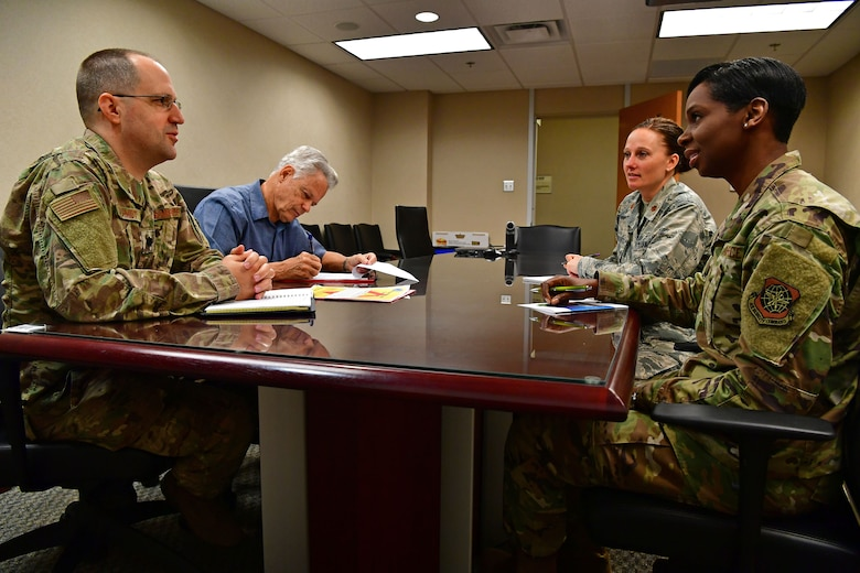 19th MDG Airmen conduct a meeting around a table.