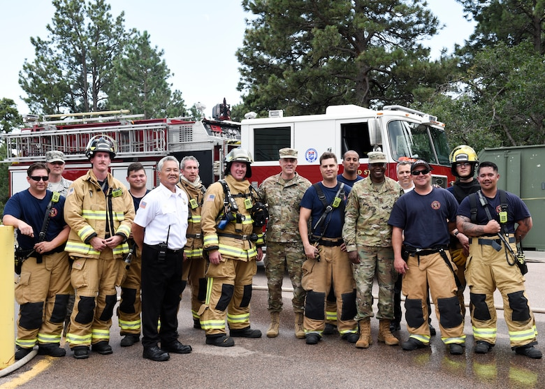 Col. Thomas Falzarano, 21st Space Wing commander (center), and Chief Master Sgt. Jacob Simmons, 21st SW command chief master sergeant, pose for a photo with the Cheyenne Mountain Air Force Station Fire Department, Sept. 6, 2019. Since becoming wing commander, Falzarano has spent time with many sections and flights across Peterson Air Force Base, Colorado, and CMAFS in order to get an in-depth perspective on what they do day to day. (U.S. Air Force photo by Airman Alexis Christian)