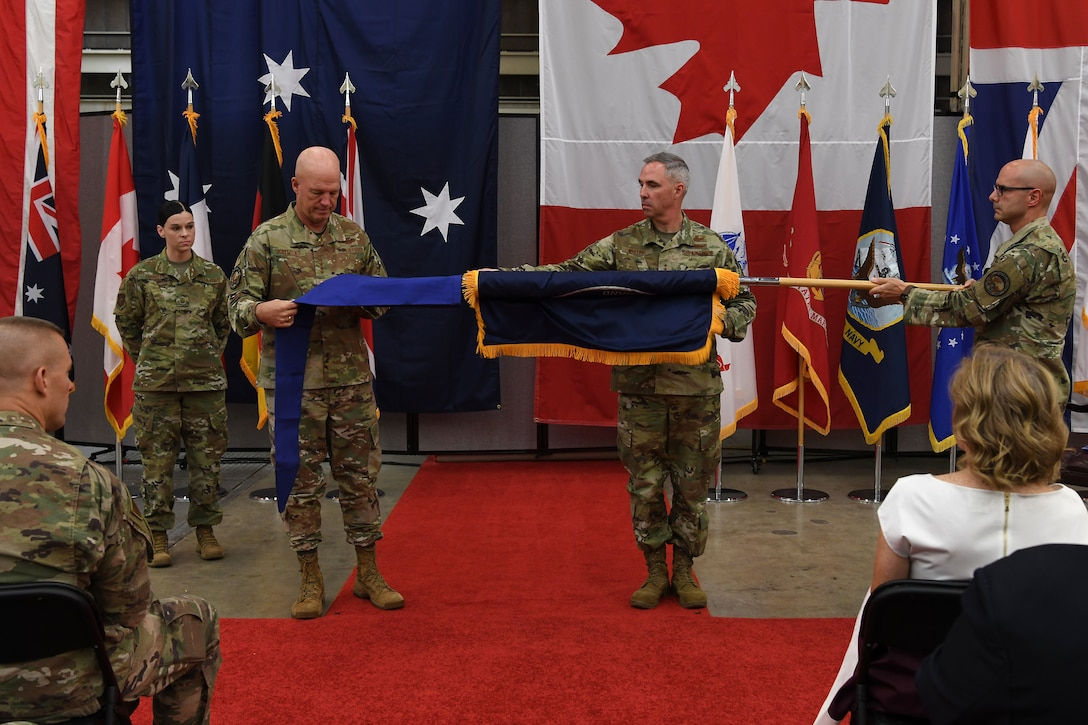 "Gen. John W. ""Jay"" Raymond, U.S. Space Command commander, unfurls the Combined Force Space Component Command flag during the CFSCC establishment ceremony Oct. 1, 2019, at Vandenberg Air Force Base, Calif."